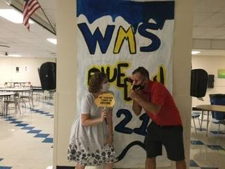 Two adults in front of WMS Blue Devils 2021 sign