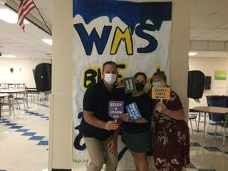 Three adults in front of WMS Blue Devils 2021 sign