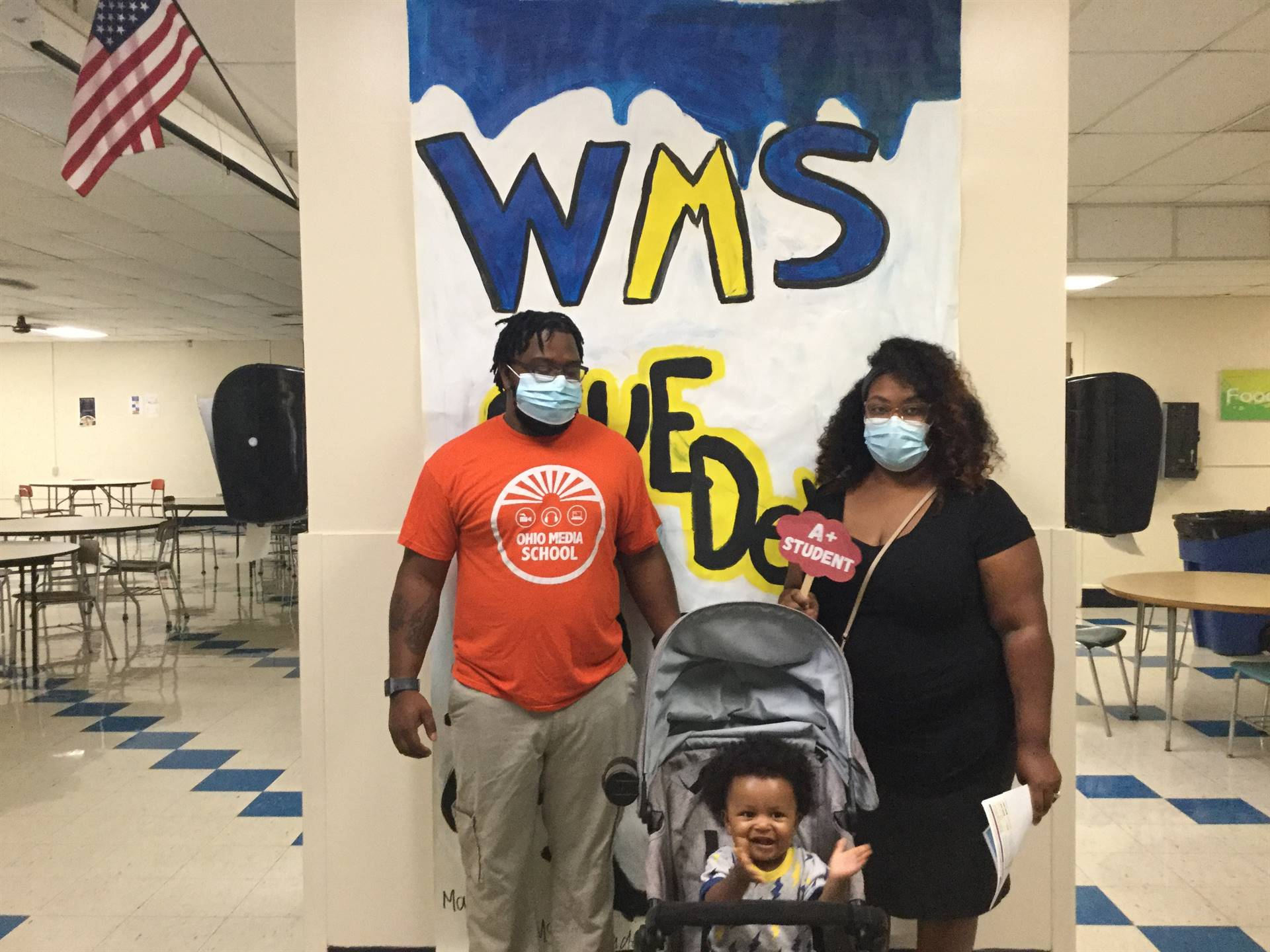Two adults and a child in front of WMS Blue Devils 2021 sign