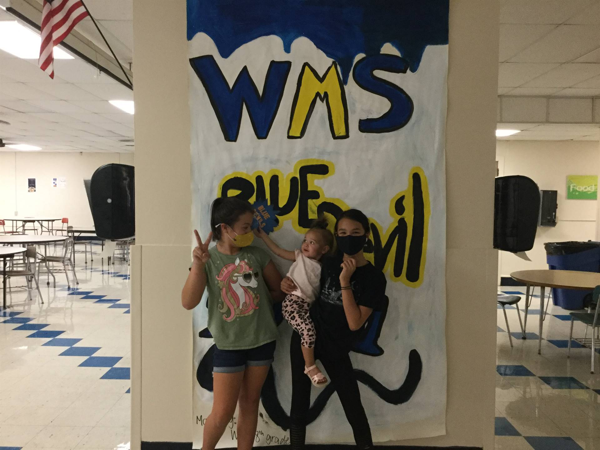 Three children in front of WMS Blue Devils 2021 sign