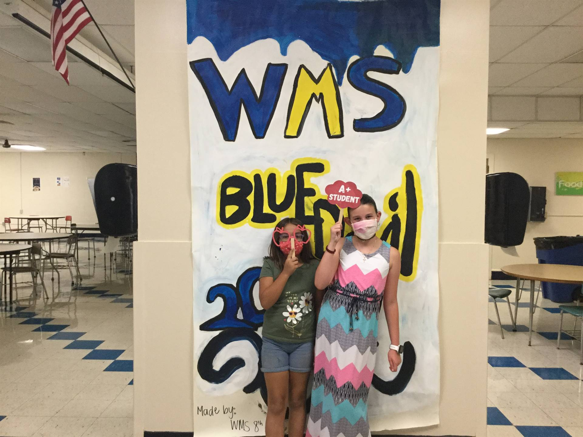 Two children in front of WMS Blue Devils 2021 sign