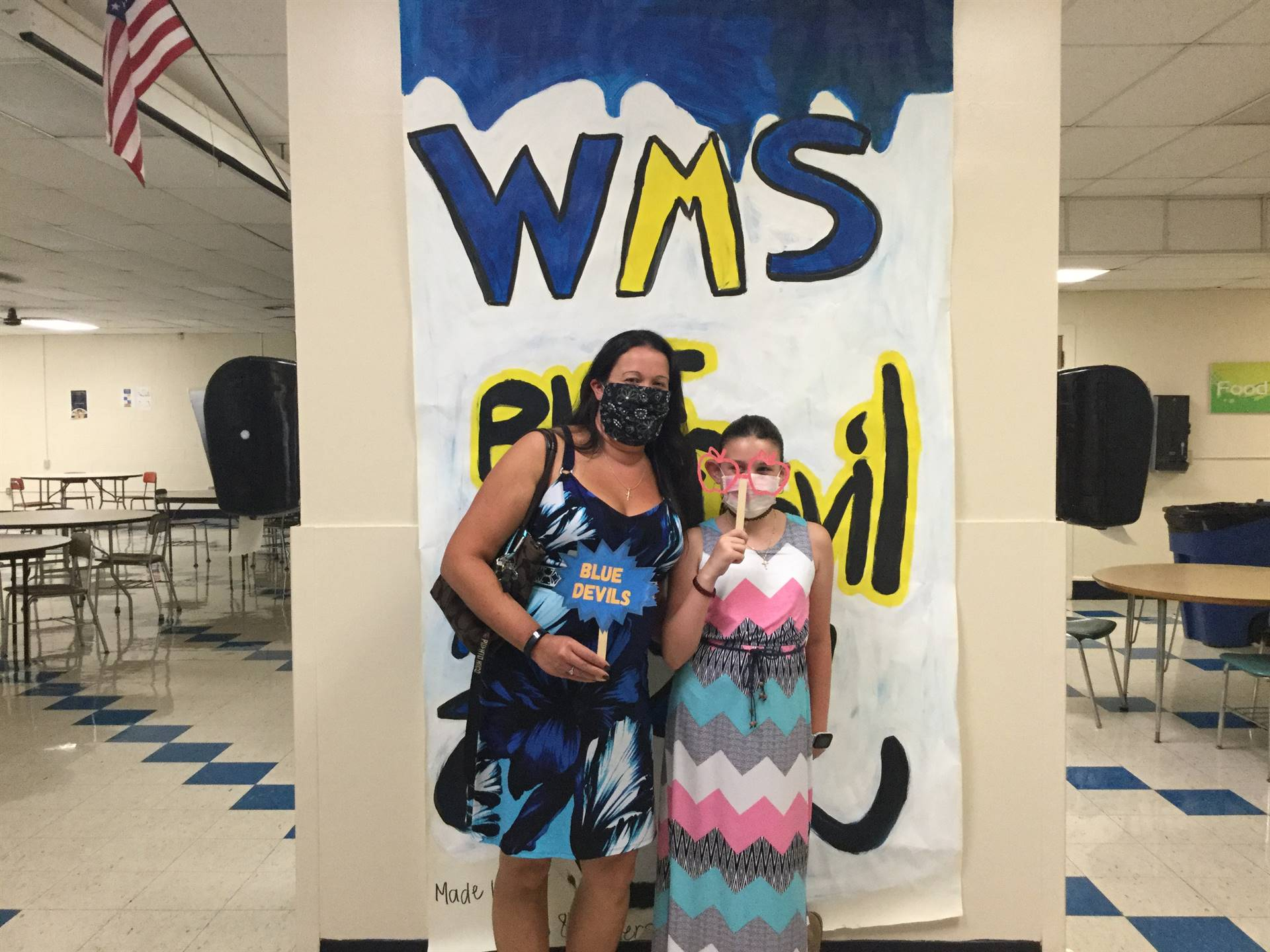 One adult and one child in front of WMS Blue Devils 2021 sign