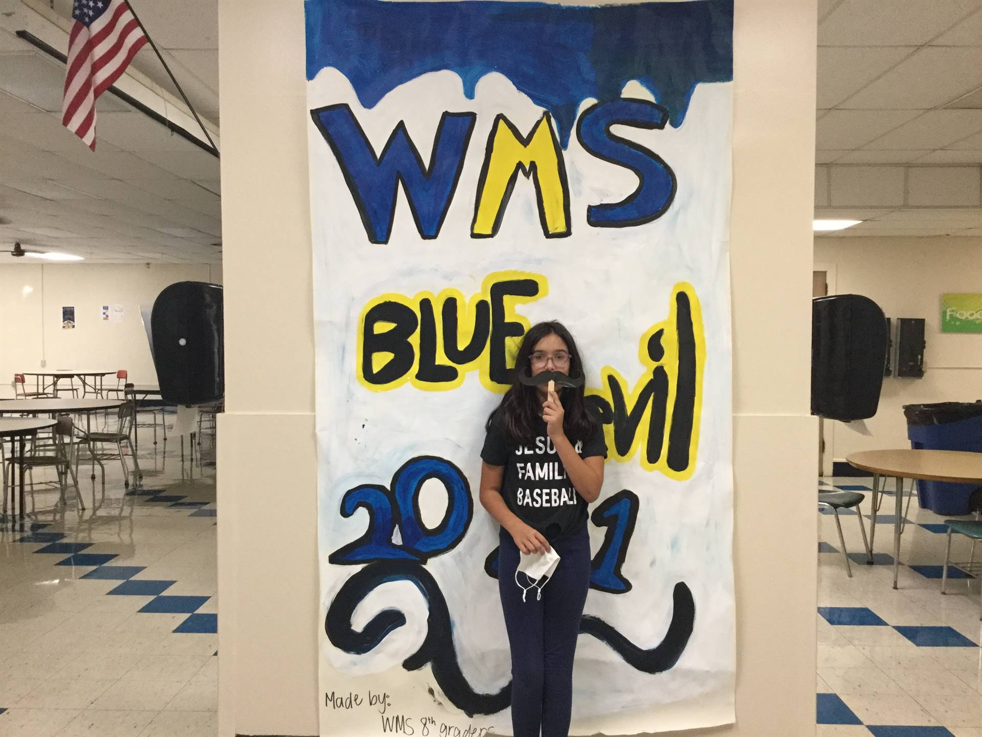 One child in front of WMS Blue Devils 2021 sign