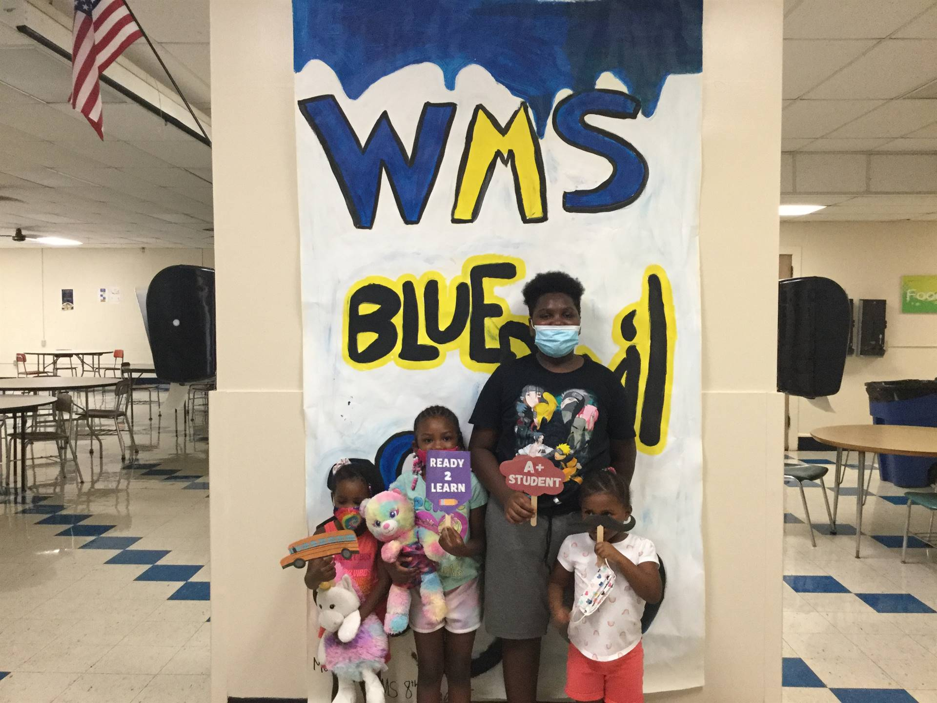 Four children in front of WMS Blue Devils 2021 sign
